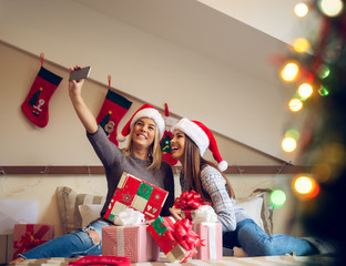 Two attractive joyful girlfriends with Santa hat sitting on the bed for Christmas holidays and taking a selfie with a raised hand.