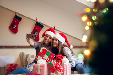 Two beautiful excited girlfriends with Santa hat sitting on the bed for Christmas holidays and taking a selfie with happiness.