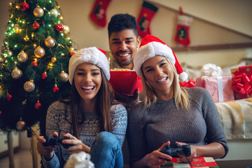 Three beautiful playful friends enjoying video games and popcorn at home for Christmas holidays.