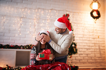Playful attractive man with Santa hat holding eye closed of his wife while she sitting on a carpet with a blanket and gift in hands for Christmas holidays.