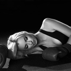 Young woman with long blonde hair and closed eyes, dressed in fitness clothing and wearing red boxing gloves, lying on dark floor illuminated by soft light. Female model posing in sports apparel.