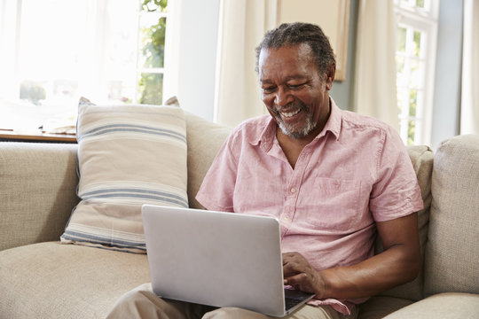 Senior Man Sitting On Sofa Using Laptop At Home Together