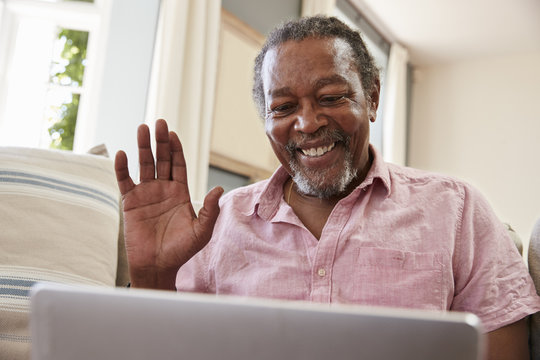 Senior Man Using Laptop To Connect With Family For Video Call