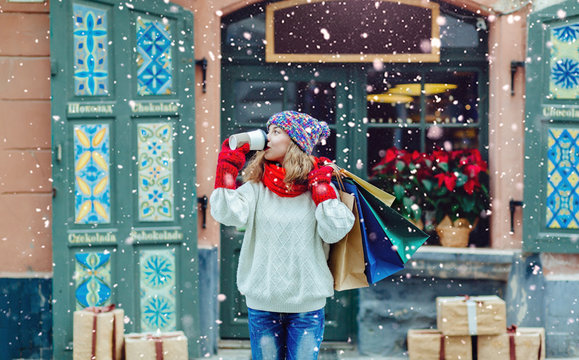 Young gorgeous lady with shopping bags drinking from disposable cup. Happy woman near the shop with gifts dressed in warm hat, red scarf and mittens. Vacation, weekend, takeaway drinks concept.