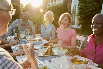 Group Of Senior Friends Enjoying Outdoor Dinner Party At Home