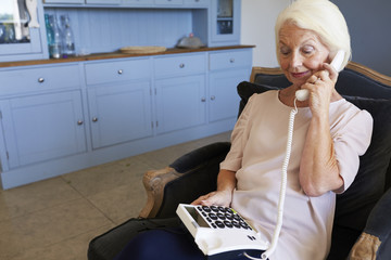 Senior Woman At Home Using Telephone With Over Sized Keys