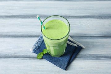 Glass with green milkshake on wooden background