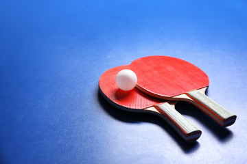 Two ping pong rackets and ball on blue background