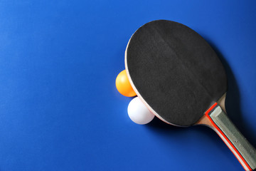 Ping pong racket and balls on blue background