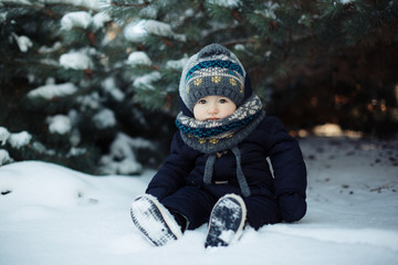 Kid in blue overalls sitting in the snow under the tree