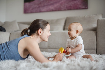 Happy baby girl with mother playing on carpet at home