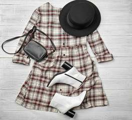 Stylish set of female clothes on wooden floor