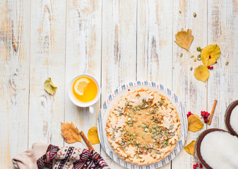 Autumn background with pumpkin pie, hot tea, yellowed leaves, book and rug. Perfect sunny autumn. A wooden light white autumn background for you. Copy Space. Place for text. Flat lay, top view