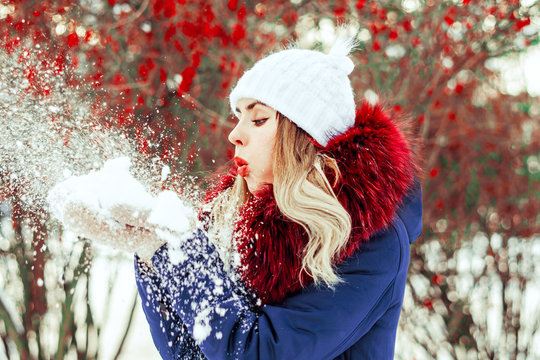 woman blowing snow in hands