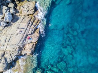 Vista aerea di scogli sul mare. Panoramica del fondo marino visto dall'alto, acqua trasparente. Nuotatori, bagnanti che galleggiano sull'acqua. Persone che prendono il sole sull'asciugamano