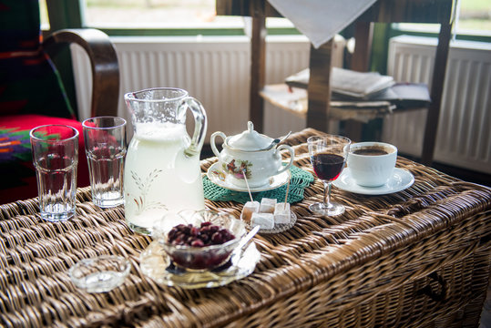 Table with Strong Turkish style coffee in a cup on a table with sugar pot, turkish delight, jar of lemonade and cranberries snaps and cranberries in the jar