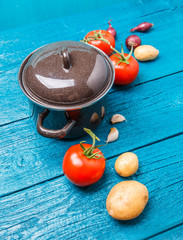 Image of iron pot for soup, tomato, potatoes, onions