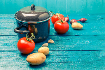 Toned photo of iron pot for soup, tomato, potatoes, onions