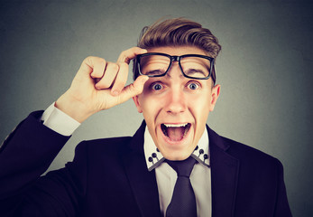 Surprised young business man taking of glasses