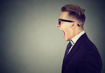 Side profile portrait of an angry business man screaming