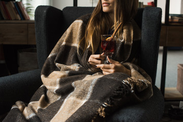 girl sitting in armchair with mulled wine