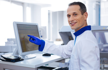 Unstoppable progress. Handsome smart researcher touching the sensor screen of cutting edge medical equipment and smiling while looking straight