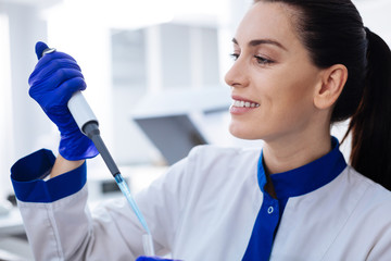 Right dosage. Portrait of friendly smiling laboratory assistant who holding pipette looking at it  and wondering