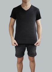 Black stretched t shirt and black shorts on a young man template on grey background.