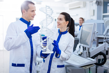 Abnormal DNA.   Pleased genuine Mal and female laboratory assistants want to find out mutation while  looking at each other and beaming