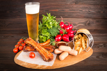 Beautiful composition: Beer, pork ribs, sausages, radish, french fries, cherry tomatoes, sauce.