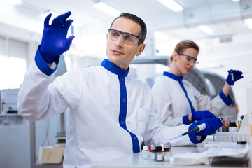 Advanced medication.  Kind budding male scientist placing the hand with pipette on the table and holding up the medication sample while wearing lab coat