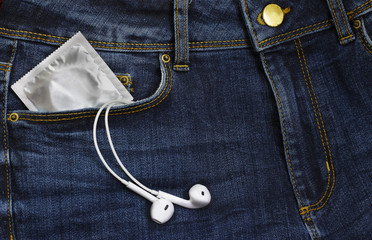 Condoms in package and headphones in jeans