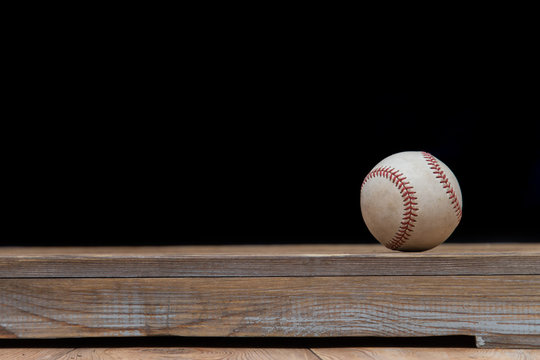 Baseball on a old rustic wooden desk with partial blur background