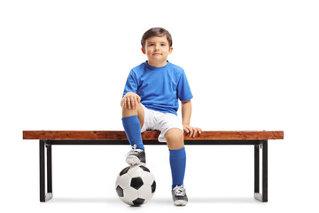 Little footballer sitting on a wooden bench
