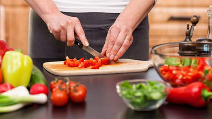 Woman chopping vegetables for a salad - closeup on hands