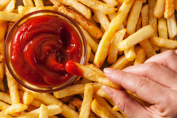 Hand dipping french fries in tomato sauce or ketchup