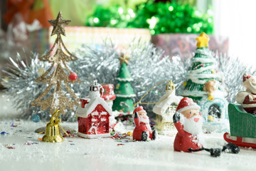 Cute happy Santa Claus dolls and Christmas props decorations on christmas snow field background