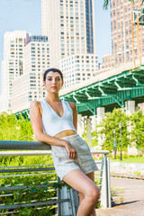 Woman Casual Summer Fashion in New York. Young pretty girl wearing white deep v neck crop tank top, shorts, standing by metal fence at street park, relaxing. High apartment buildings on background.