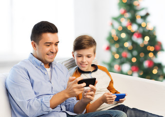 happy father and son with smartphones at christmas