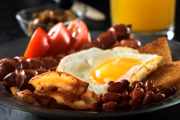 Bacon, grilled sausages, fried egg, beans, beans, toast, tomatoes, mushrooms fresh juice - full English breakfast. Black background. Morning light