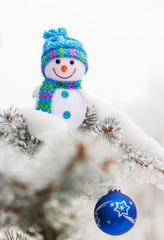 Little funny snowman and toy-ball, on Christmas tree. Close-up