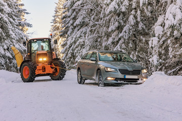 The tractor pulls a snowy car in the snow in winter landscape in Sumava. South Czech.