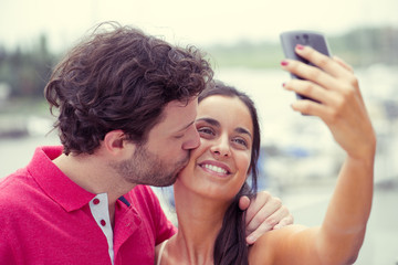 Man and woman posing for selfie taken with smart phone
