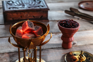 coals for Shisha Smoking are in the Golden bowl, made in the shape of a Lotus on the background of Smoking accessories