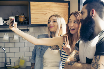 Friends posing together for selfie with smartphone