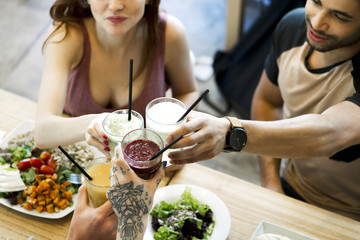 Friends clinking glasses while dining together in restaurant