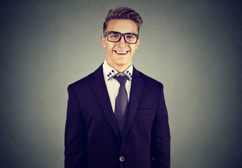 Laughing funny looking handsome businessman in glasses on gray wall background
