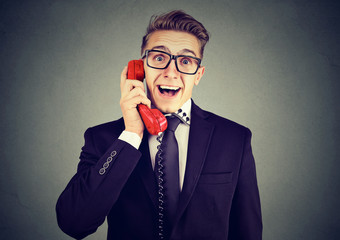 Happy business man receiving good news winning on the phone isolated on gray wall background