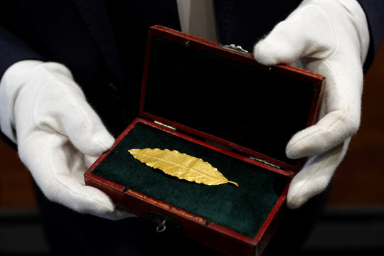 An auctioneer displays a gold laurel leaf from French Emperor Napoleon's imperial crown at the office of the Osenat auction house in Paris
