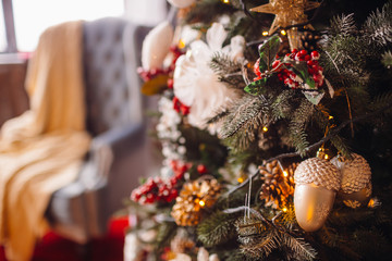 Original decor in form of acorn and toys hangs on rich Christmas tree standing in a cosy room